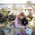 Flicka med hund i knät.