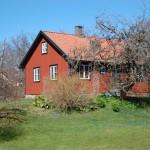 Ett litet rött hus med trädgård.