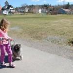 Flicka med hund i koppel.